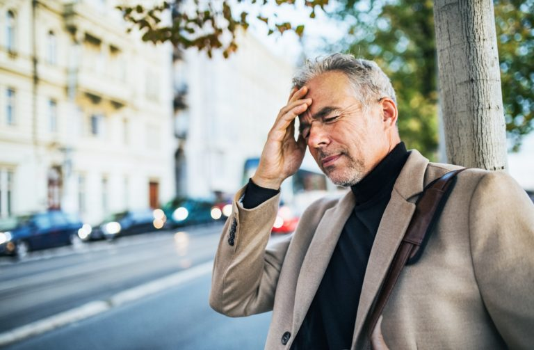 Mature businessman in pain standing on a street in city, holding forehead.